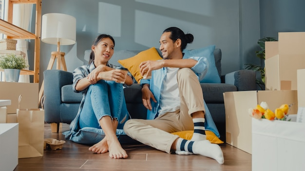 Happy asian young couple man and woman sit at new home drink coffee and talk with carton package box storage