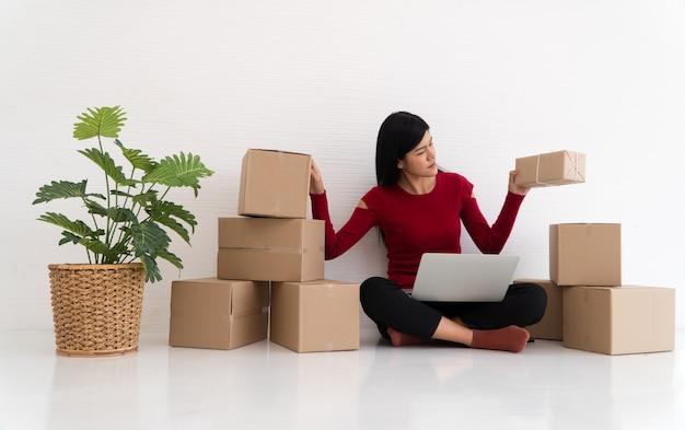 幸せなアジアの若い起業家、自宅のオンラインショッピングストアからの注文を確認した後、販売成功のための笑顔