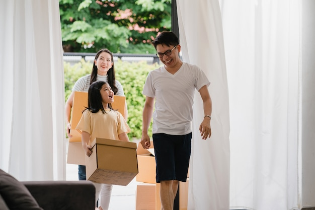 Happy asian young family bought new house. japanese mom, dad, and child smiling happy hold cardboard boxes for move object walking into big modern home. new real estate dwelling, loan and mortgage.