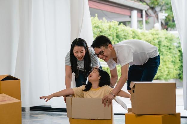新しい家に移動して笑って楽しんで幸せなアジアの若い家族。日本人の親の母親と父親は、段ボール箱に座っている小さな女の子に乗って興奮して支援を笑っています。新しいプロパティと移転。
