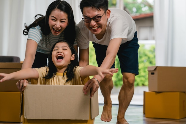 Happy asian young family having fun laughing moving into new home. japanese parents mother and father smiling helping excited little girl riding sitting in cardboard box. new property and relocation.