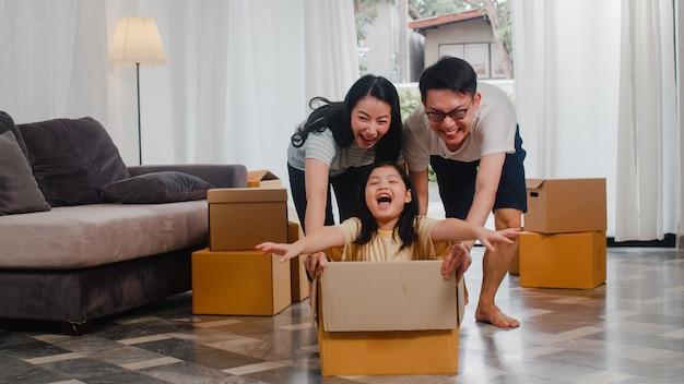 Giovane famiglia asiatica felice divertendosi ridendo entrando nella nuova casa. genitori giapponesi madre e padre che sorridono aiutando la guida emozionante della bambina che si siede in scatola di cartone. nuova proprietà e trasferimento.