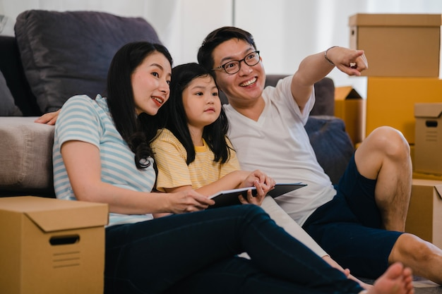 Happy asian young family homeowners bought new house. chinese mom, dad, and daughter embracing looking forward to future in new home after moving in relocation sitting on floor with boxes together.