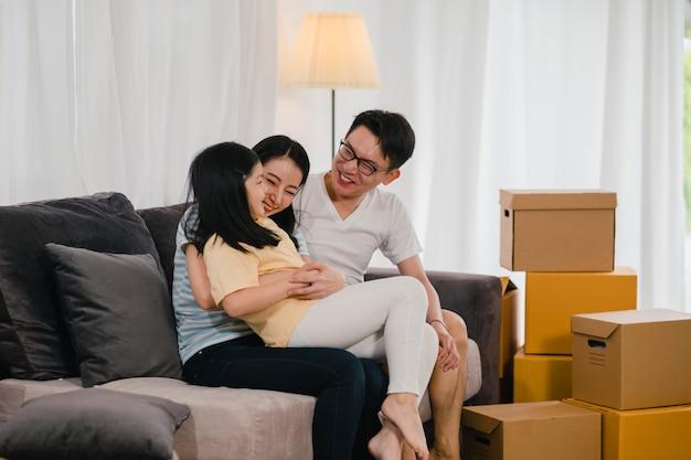 幸せなアジアの若い家族の住宅所有者が新しい家を買いました。日本人のお母さん、お父さん、娘は一緒に箱を置いてソファーに座って転居した後、新しい家で将来を楽しみに抱きしめています。