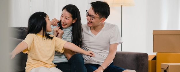 Happy asian young family homeowners bought new house. japanese mom, dad, and daughter embracing looking forward to future in new home after moving in relocation sitting on sofa with boxes together.
