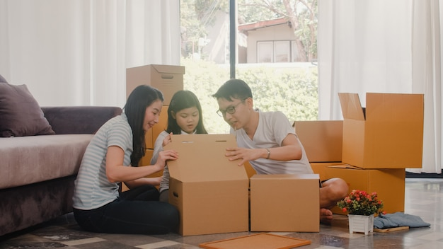 Happy asian young family relocation removals settle in new home. chinese parents and kids open cardboard box or parcel unpacking in living room on moving day. real estate dwelling, loan and mortgage.