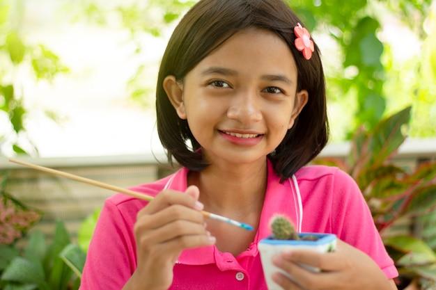 Счастливая азиатская молодая девушка рисует цвет на горшке с кактусом в природе