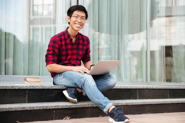 屋外でラップトップを使用して格子縞のシャツを着た幸せなアジアの若い男