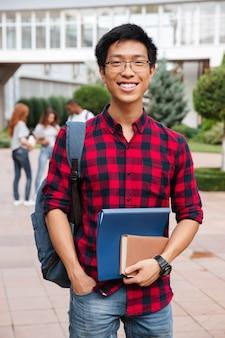 屋外に立っているバックパックとメガネと格子縞のシャツの幸せなアジアの若い男の学生