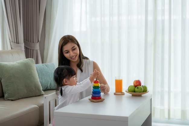 Happy asian young mother and daughter playing with wooden colorful toys, early education at home. parenthood or love and bonding expression concept.