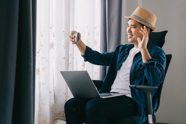 Счастливый азиатский молодой подросток человек дома держит телефон, глядя на экран, машет рукой, видео звонит другу на расстоянии онлайн в мобильном приложении чата с помощью приложения для видеочата на смартфоне.