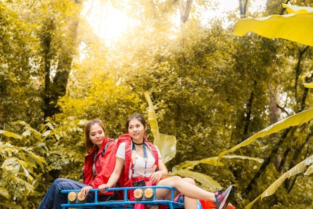 Счастливые азиатские молодые путешественники с автомобилем 4wd с дороги в лесу