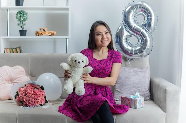 Giovane donna asiatica felice in vestito bello che si siede su un divano con il mazzo di fiori che tiene l'orsacchiotto che sorride allegramente nel soggiorno luminoso per celebrare la giornata internazionale della donna