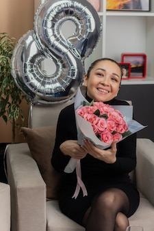 Happy asian young woman in black dress sitting on a chair with a bouquet of flowers smiling cheerfully in light living room celebrating international women's day