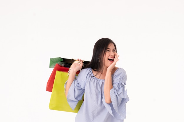 Happy asian young woman carrying shopping bags isolated