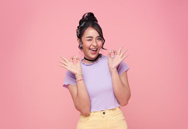 幸せなアジアの若い女性のジェスチャーやピンクの背景に分離された手を示しています。