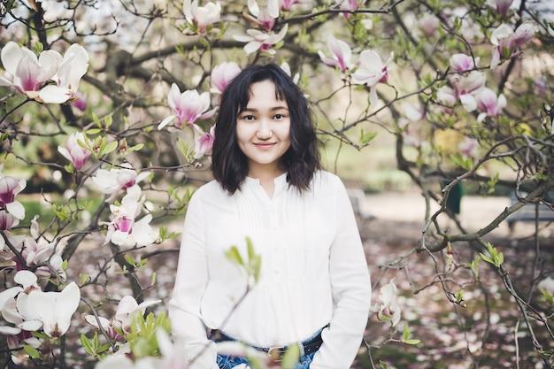 咲くモクレンの木の下で白いブラウスで幸せなアジアの若い女性