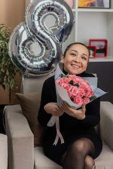 国際女性の日を祝う明るいリビングルームで元気に笑う花の花束と椅子に座っている黒いドレスを着た幸せなアジアの若い女性