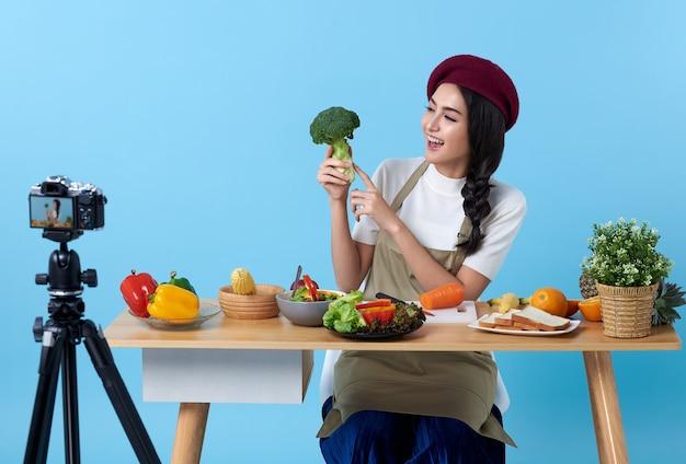 Счастливая азиатская молодая женщина в модном стиле и съемке видео с камерой, готовящей здоровую еду, - блоггер, представляющий для социальных людей. она является влиятельным лицом в социальных сетях.