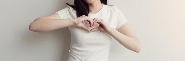 심장 모양에 그녀의 손을 만드는 행복 한 아시아 젊은 여자