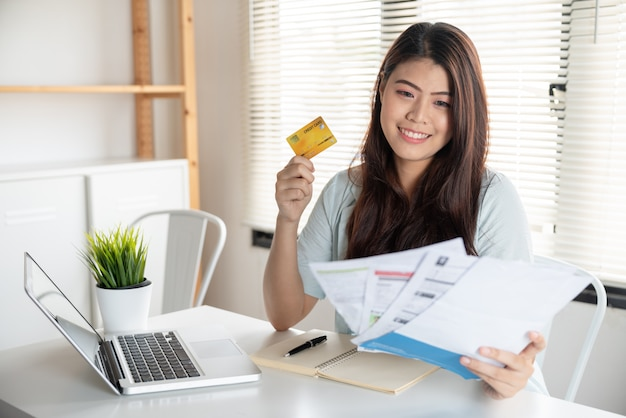 Happy asian young woman smiling holding so many expenses bills
