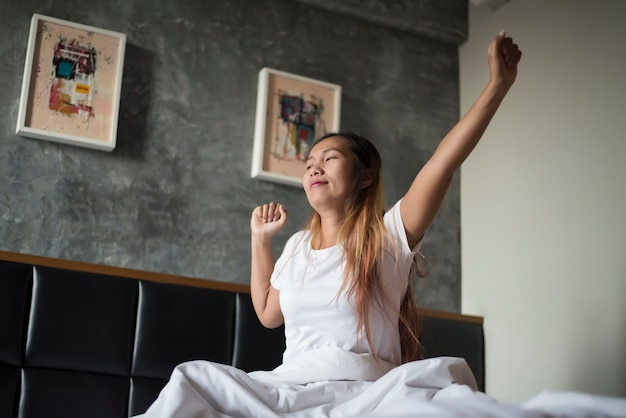 Happy asian young woman stretching after waking up while in the bedroom