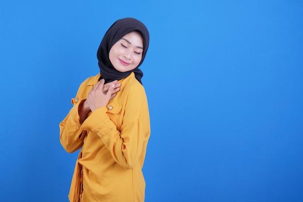 Счастливая азиатская молодая женщина трогает грудь двумя руками и закрывает глаза