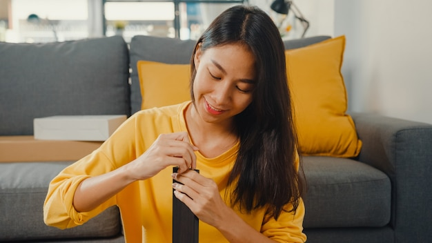행복 한 아시아 젊은 여자 상자를 풀고 새 가구를 조립하는 지침을 읽고