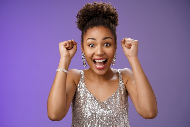 Happy astonished african american woman in silver fashionable dress winning first prize gladly celebrating raising clenched fists dancing triumphing happily having fun, standing blue background.