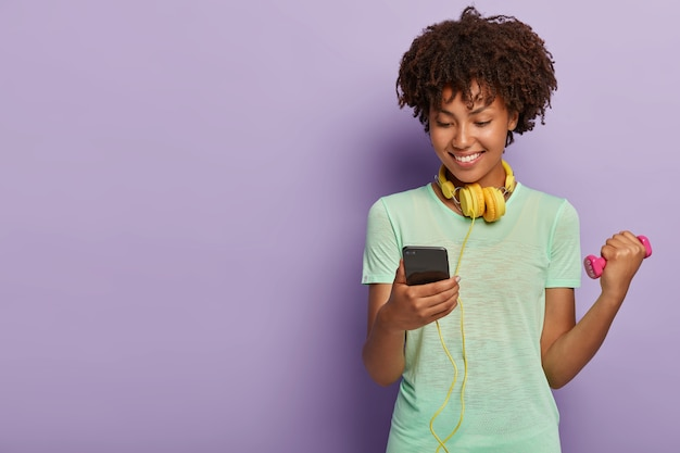 Felice atleta femminile ha acconciatura afro, si allena con manubri, ascolta musica tramite le cuffie, guarda il telefono, vestito con una maglietta casual