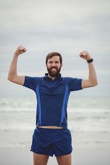 Atleta felice in piedi sulla spiaggia con le mani alzate