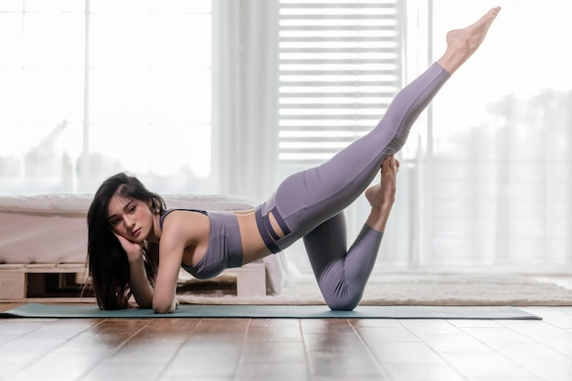 Happy athletic asian woman practice yoga stretching pose for stretching muscle for warm up