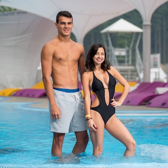 Happy athletic guy and girl with a perfect figure near the swimming pool on luxury mountain resort with blurred background