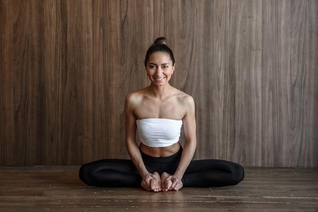 나비 포즈에 앉아 나무 배경에서 요가 연습 행복 운동 근육 요기 여자