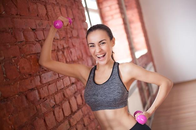 Счастливая спортивная стройная женщина в спортивной одежде с гантелями смотрит на камеру в тренажерном зале или дома