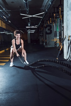 Happy athletic woman exercising with battle ropes in gym
