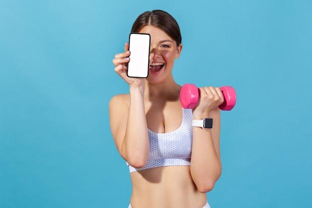 빈 화면 스마트폰과 분홍색 덤벨을 들고 흰색 스포츠 상단에 행복 운동 여자