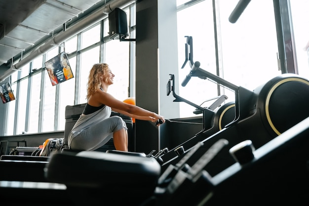 Happy athletic woman is engaged in rowing in the gym for muscle training concept of fitness and weig...