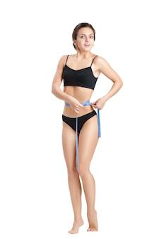 흰색에 다이어트 후 파란색 측정 테이프로 그녀의 허리를 측정하는 행복 운동 여자