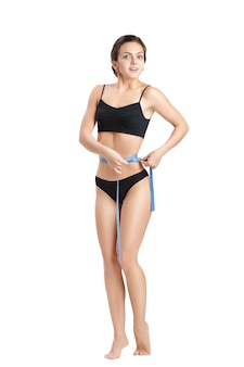 Happy athletic  woman measuring her waist by blue measure tape after a diet on a white
