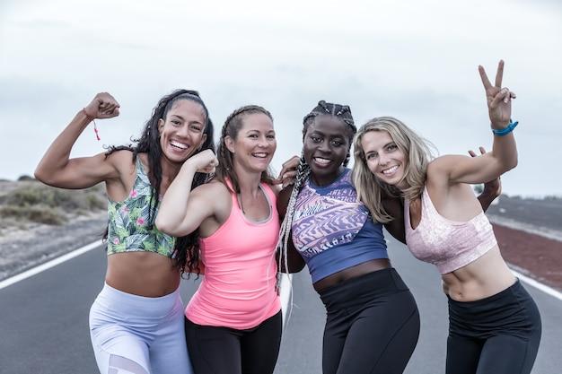 Счастливые атлетические женщины в спортивной одежде жестикулируя и усмехаясь