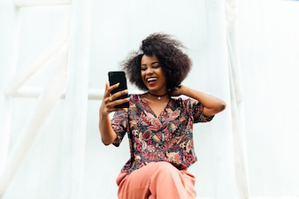 Happy attractive african woman, smiling cheerfully while looking at mobile phone screen.