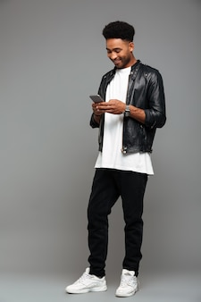 スマートフォンでメッセージを入力して幸せな魅力的なアフロアメリカン男