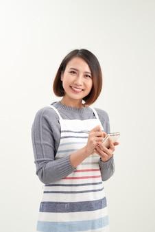エプロンの書き込み順序とカメラを見て幸せな魅力的なアジアの女性ウェイター