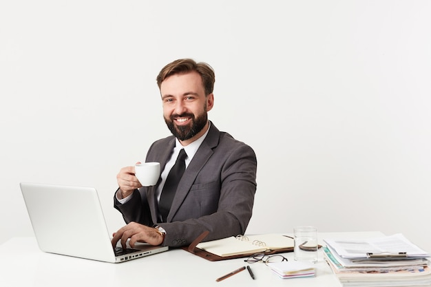 Happy attractive bearded businessman with short brown hair holding cup of tea and looking joyfully at front, working with laptop and typing letter to his partners