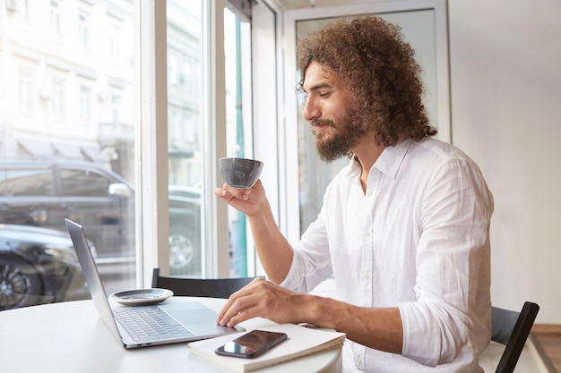 Happy attractive bearded guy sitting at table next to window with laptop, looking at screen joyfully and having cup of tea, wearing white shirt