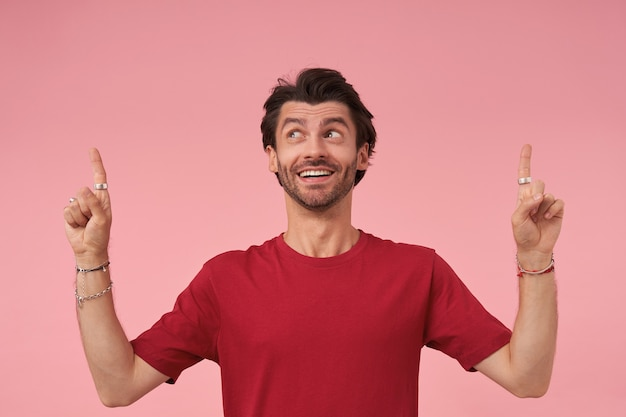 Happy attractive bearded male wearing red t-shirt, looking upwards and pointing up with forefingers, standing, contracting forehead and raising eyebrows with wide smile