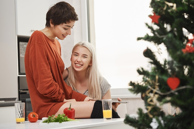 Happy attractive blonde girl holding tablet and smiling at camera while sitting next to her lovely girlfriend in kitchen near christmas tree. women laughing over article they read via gadget.