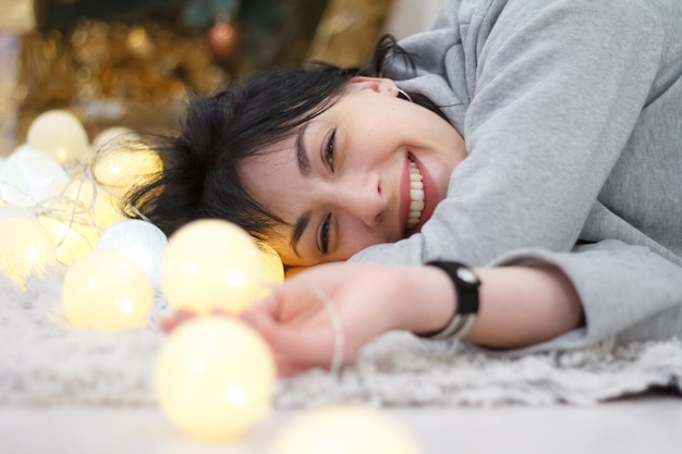 Happy attractive brunette girl lying at home with a garland of lights