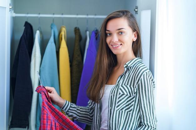 スタイリッシュな服や家のものとワードローブクローゼットから衣装を選択する幸せな魅力的なブルネットの女性